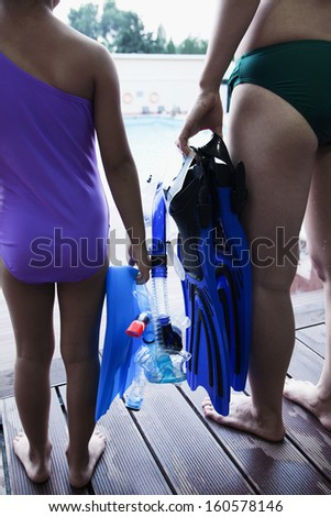 Mother and daughter holding flippers and snorkeling mask by pool - stock photo