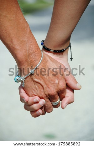 Mother and daughter holding hands. - stock photo