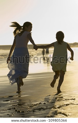 Mother and daughter holding hands and running on the beach - stock photo