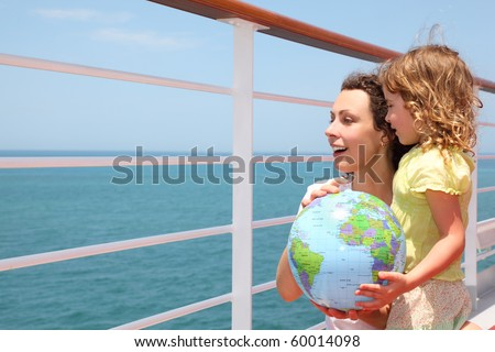 mother and daughter holding inflatable globe on cruise liner deck, half body - stock photo