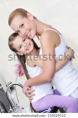 Mother and daughter hug each other in bathroom - stock photo