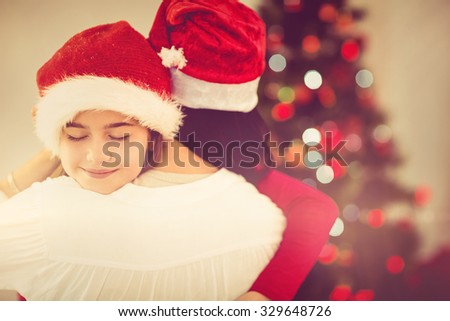 Mother and daughter hugging at christmas at home in the living room - stock photo