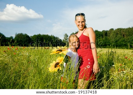 Mother and daughter in a sunlit field with wild flowers hugging each other - stock photo