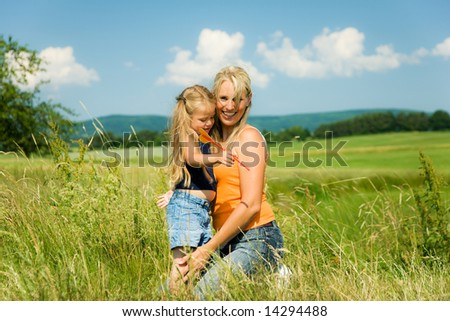 Mother and daughter in a sunlit meadow hugging each other - stock photo