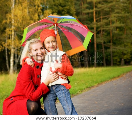 Mother and daughter in autumn forest - stock photo