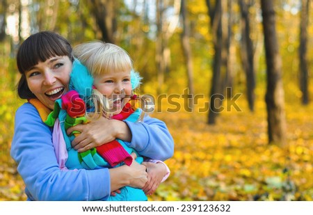 Mother and daughter in autumn park.