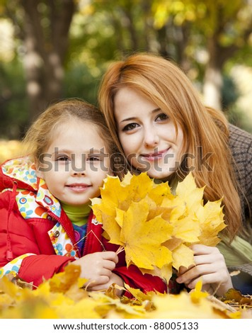 Mother and daughter in autumn yellow park.