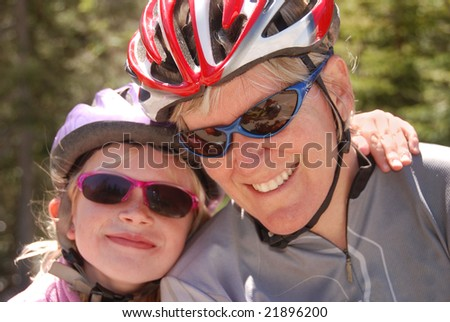 Mother and daughter in bicycle helmets. The daughter has her arm thrown around her mother.