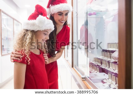 Mother and daughter in Christmas attire looking at jewelry display in shop - stock photo
