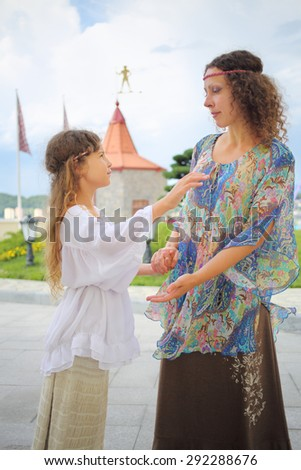 Mother and daughter in ethnic dress holding hands near the medieval castle  - stock photo