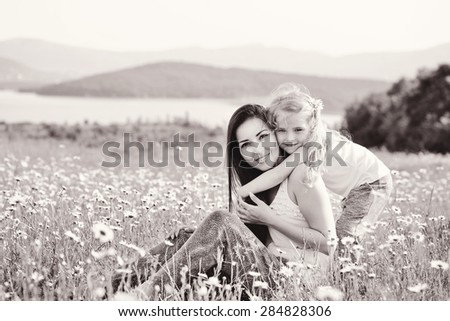 mother and daughter in field of daisies - stock photo