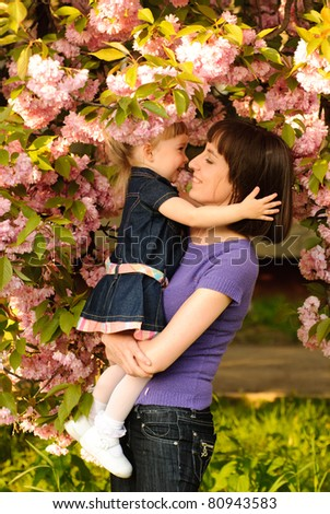 Mother and daughter in garden, under the sakura tree. Spring.