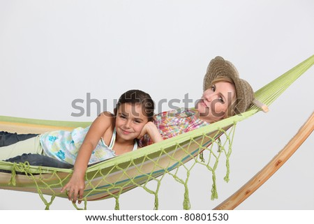 Mother and daughter in hammock - stock photo