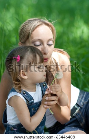 Mother and daughter in jeans with dandelion outdoor - stock photo