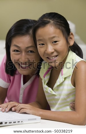 Mother and Daughter in living room Using Laptop Together, portrait - stock photo