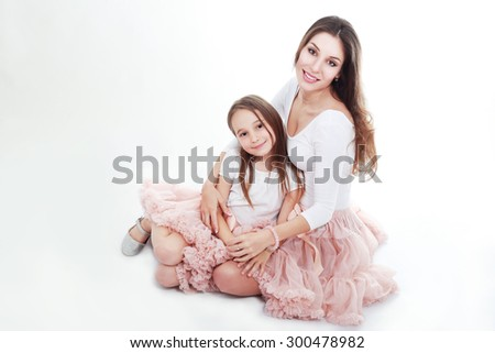 mother and daughter in same outfits posing on studio hugging - stock photo