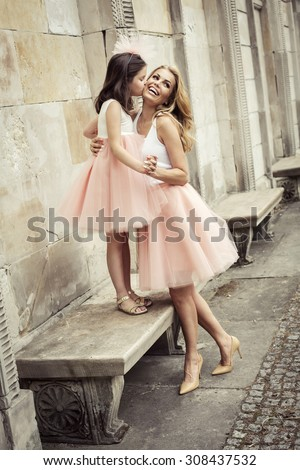 Mother and daughter in same outfits wearing tutu skirts - stock photo