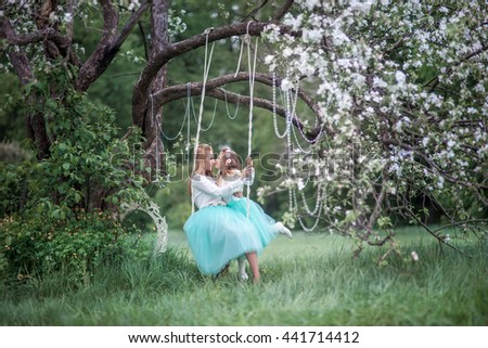 Mother and daughter in spring blossom garden