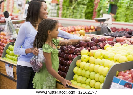 Mother and daughter in supermarket produce section - stock photo