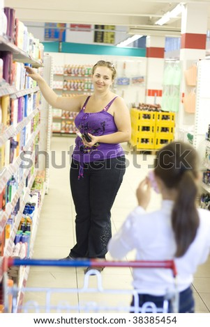 Mother and daughter in supermarket. Shopping. Girl showing to mother