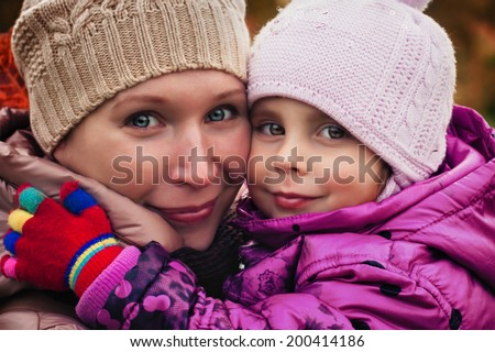 Mother and daughter in the autumn park. - stock photo