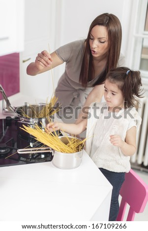 Mother and daughter in the kitchen - stock photo