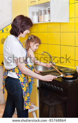 Mother and daughter in the kitchen, near the plate - stock photo