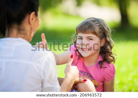 Mother and daughter in the park having fun - stock photo