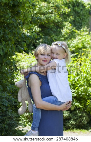 Mother and daughter in the park on summer day - stock photo