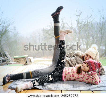 mother and daughter in winter clothes on the porch of a country house. - stock photo