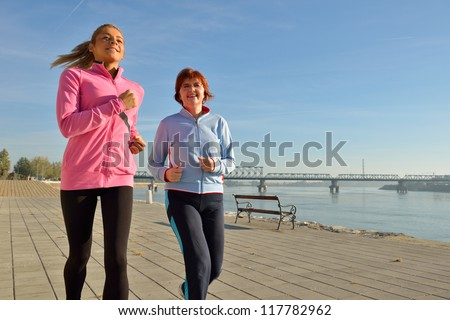 Mother and daughter jogging on coasts - stock photo