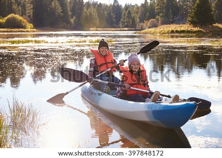 Mother and daughter kayaking on lake, front view, close-up - stock photo