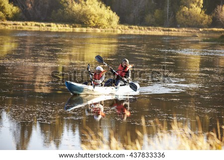 Mother and daughter kayaking together on a lake, front view - stock photo
