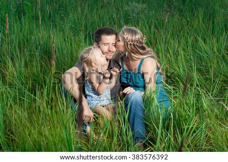Mother and daughter kissing daddy outdoors. Happy family. - stock photo