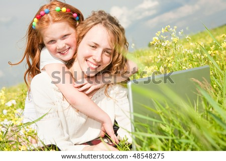 mother and daughter lay on a grass with a notebook - stock photo