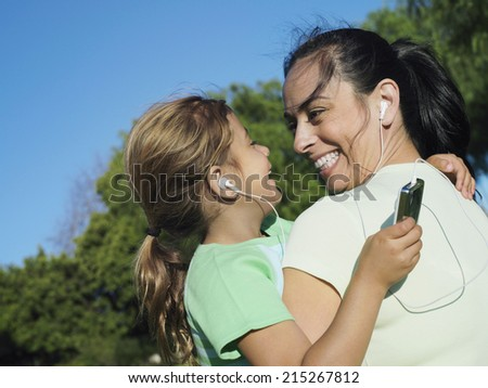 Mother and daughter (6-8) listening to MP3 player, sharing headphones, smiling, close-up (tilt) - stock photo