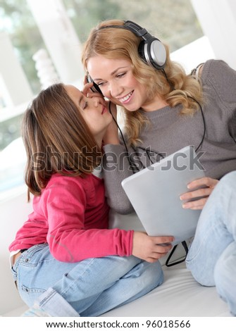 Mother and daughter listening to music - stock photo