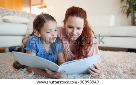 Mother and daughter looking at a magazine together - stock photo