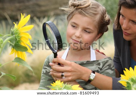 Mother and daughter looking at a sunflower with a magnifying glass - stock photo