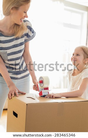 Mother and daughter looking at each other while packing cardboard box at home - stock photo