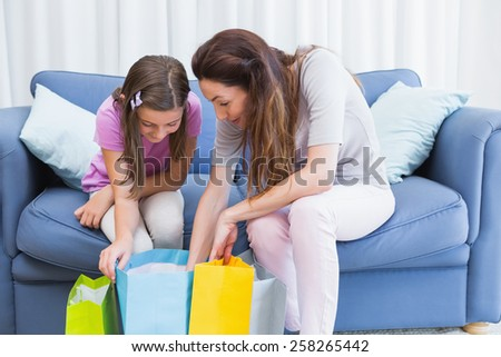 Mother and daughter looking at shopping bags at home in the living room