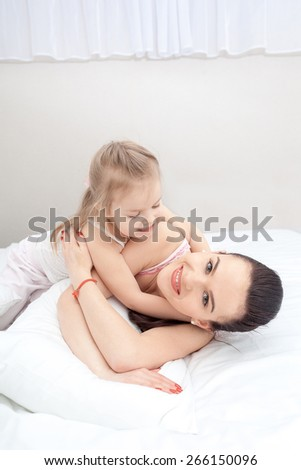 Mother and daughter lying in soft bed - stock photo