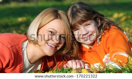 mother and daughter lying on grass - stock photo