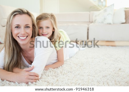 Mother and daughter lying on the floor together - stock photo