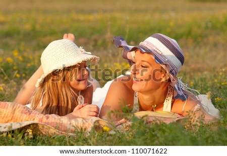 Mother and daughter lying on the meadow on sunny summer day. - stock photo