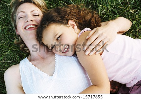 Mother and daughter lying outdoors smiling - stock photo