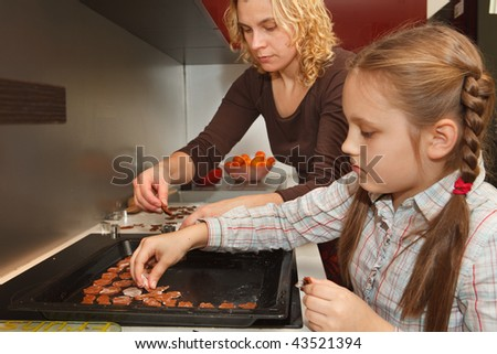 Mother and daughter make homemade gingerbread for christmas - stock photo