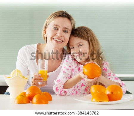 Mother and daughter make orange juice on a juicer - stock photo