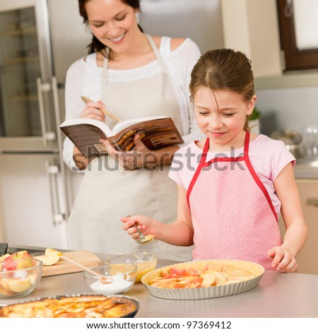 Mother and daughter making apple pie follow recipe from cookbook - stock photo