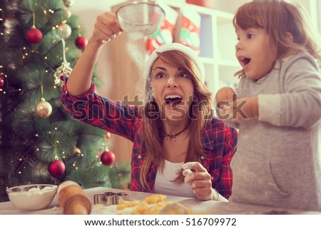 Mother and daughter making Christmas cookies and having fun. Mother sifts the flour through a sieve on the great amazement of her daughter
